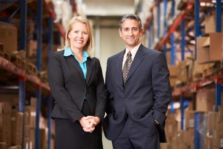 Businesswoman And Businessman In Distribution Warehouse Zdjęcie Seryjne
