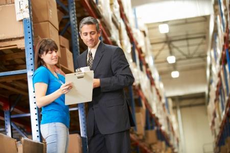control de calidad: Hombre de negocios y la trabajadora en el Almacén de distribución Foto de archivo