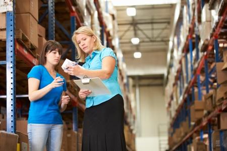 control de calidad: Empresaria Y Trabajador Mujer En Almacén de distribución