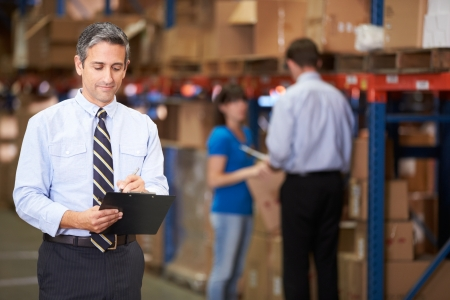 business writing: Manager In Warehouse Writing On Clipboard