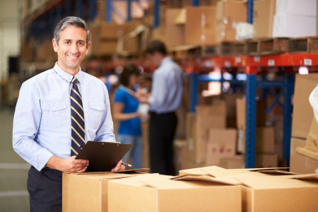 man of business: Manager In Warehouse Checking Boxes
