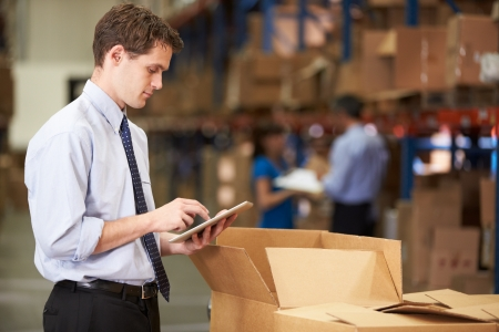 shipment: Manager In Warehouse Checking Boxes Using Digital Tablet Stock Photo