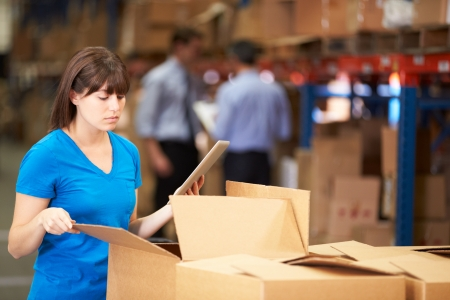 three shelves: Worker In Warehouse Checking Boxes Using Digital Tablet Stock Photo