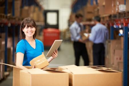 デジタル タブレットを使用してボックスをチェックする倉庫の労働者