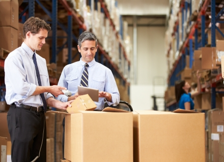barcode scanner: Businessmen Checking Boxes With Digital Tablet And Scanner Stock Photo