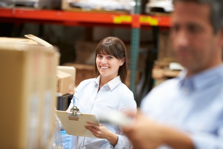 warehouse worker: Manager In Warehouse With Worker Scanning Box In Foreground Stock Photo
