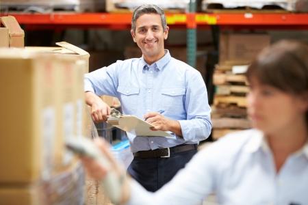 フォア グラウンドでボックスをスキャン労働者と倉庫のマネージャー