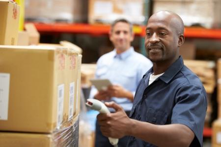 Manager In Pakhuis Met Arbeider Scanning Doos In Voorgrond Stockfoto