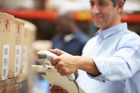 Arbeider Scanning pakket In Pakhuis Stockfoto