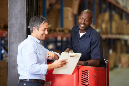 Fork Lift Truck Operator Talking To Manager In Warehouse photo