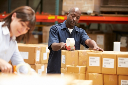 sealing tape: Workers In Warehouse Preparing Goods For Dispatch