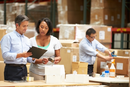 packaging industry: Workers In Warehouse Preparing Goods For Dispatch