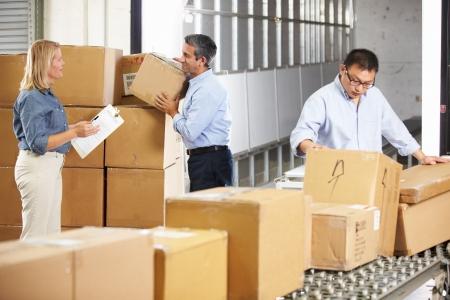 Werknemers controleren Goederen op band in distributiecentrum Stockfoto