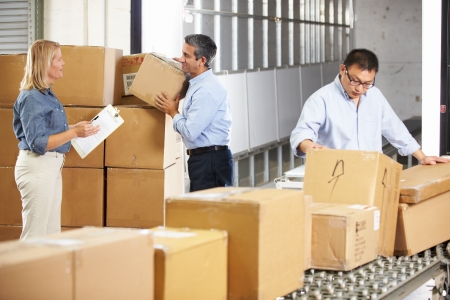 packing: Workers Checking Goods On Belt In Distribution Warehouse