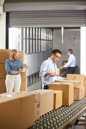 cinta transportadora: Trabajadores Comprobación de Mercancías En Cinturón En Almacén de distribución Foto de archivo