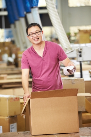 sealing tape: Worker In Warehouse Preparing Goods For Dispatch Stock Photo