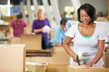 packing tape: Workers In Warehouse Preparing Goods For Dispatch