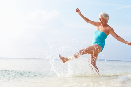 Senior Woman Splashing In Sea On Beach Holiday Stock Photo - 24491416