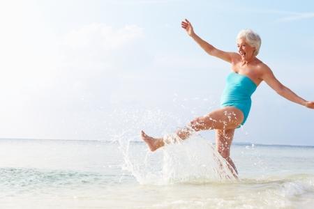 woman beach: Senior Woman Splashing In Sea On Beach Holiday