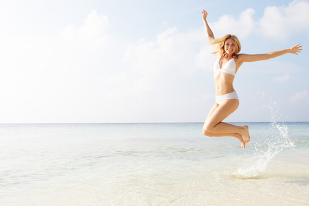 woman jumping: Woman Jumping In The Air On Tropical Beach Stock Photo