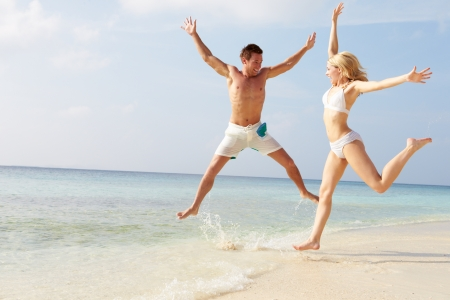 bikini couple: Couple Jumping In The Air On Tropical Beach Stock Photo