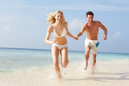 personas corriendo: Pares que se ejecutan a través de Ondas en la playa de vacaciones