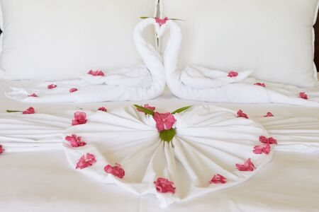 Hotel Bedroom With Flowers Arranged On Sheets Imagens