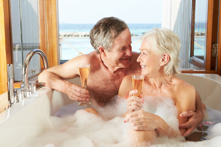 Senior Couple Relaxing In Bath Drinking Champagne Together photo