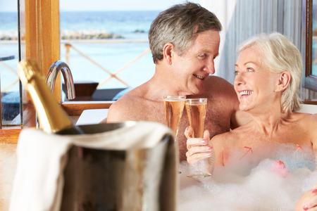 haciendo el amor: Senior pareja se relaja en baño bebe Champán Juntos