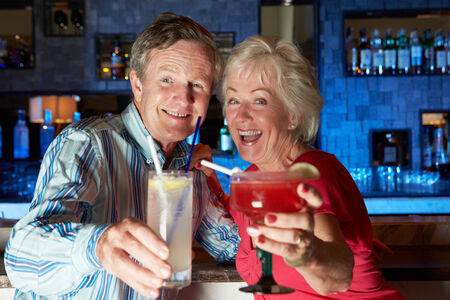 Senior Couple Enjoying Cocktail In Bar photo