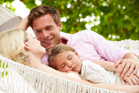 Family Relaxing In Beach Hammock With Sleeping Daughter photo
