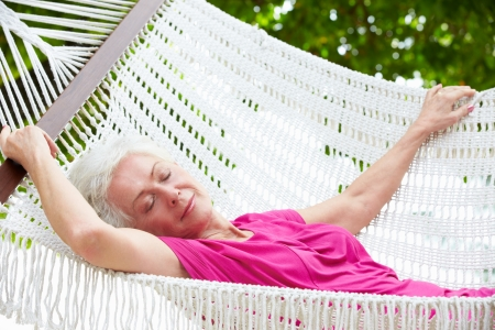 Senior Woman Relaxing In Beach Hammock photo