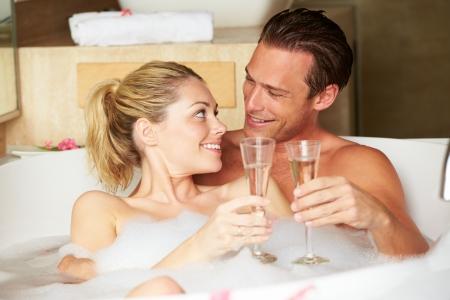 haciendo el amor: Pareja en el baño relajante Bebiendo Champagne Juntos