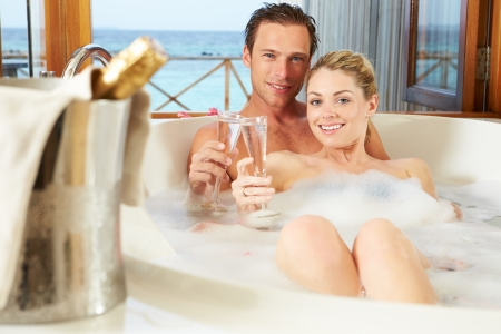 Couple Relaxing In Bath Drinking Champagne Together photo