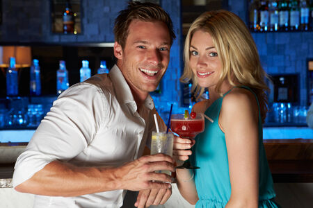 Couple Enjoying Cocktail In Bar photo