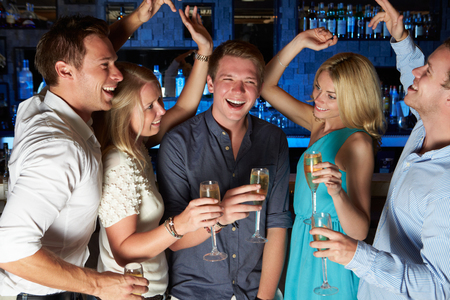 Group Of Friends Enjoying Glass Of Champagne In Bar photo
