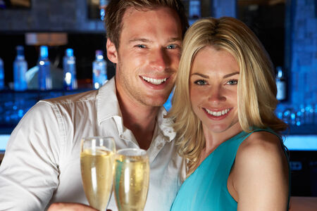 Couple Enjoying Glass Of Champagne In Bar photo