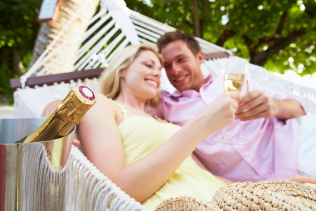Couple Relaxing In Beach Hammock Drinking Champagne photo