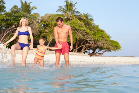 Family Splashing In The Sea On Tropical Beach Holiday photo