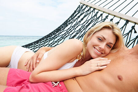 Couple Relaxing In Beach Hammock photo