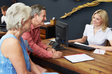 hotel worker: Hotel Receptionist Helping Senior Couple To Check In Stock Photo