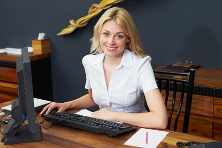 Hotel Receptionist Working At Computer photo