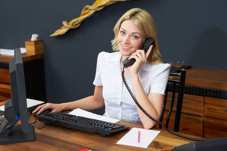 hotel receptionist: Hotel Receptionist Using Computer And Phone Stock Photo