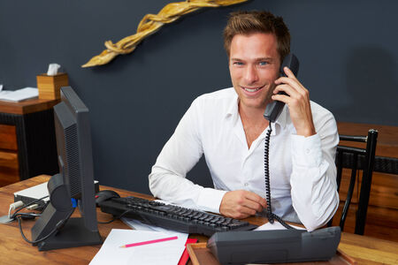 answering call: Hotel Receptionist Using Computer And Phone Stock Photo