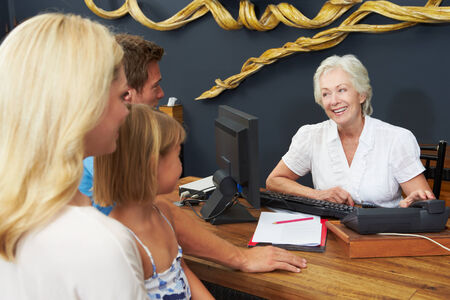 check in: Hotel Receptionist Helping Family To Check In