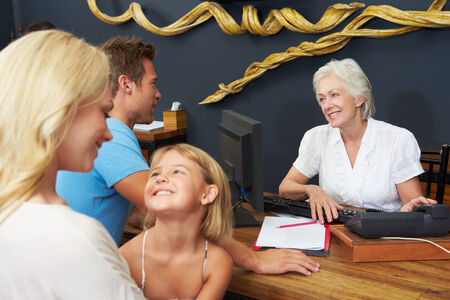 Hotel Receptionist Helping Family To Check In photo