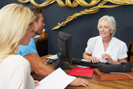 Hotel Receptionist Helping Couple To Check In photo