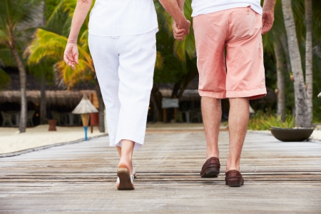 Detail Of Senior Couple Walking On Wooden Jetty photo