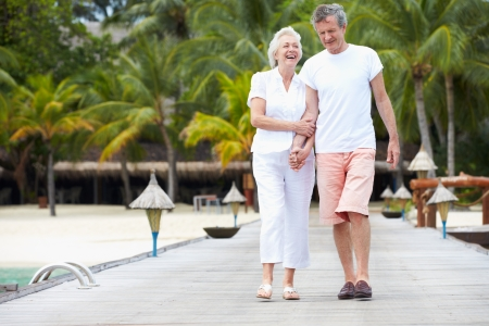 Senior Couple Walking On Wooden Jetty photo