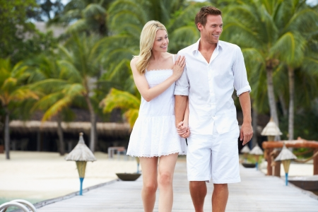 Couple Walking On Wooden Jetty photo